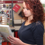red-haired woman looking at a book