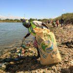 woman picking up trash on Haitian beach