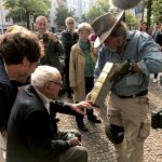Tom Tugend touches four brass-plated cubes held by artist Gunter Demnig at a ceremony in Berlin on July 13.